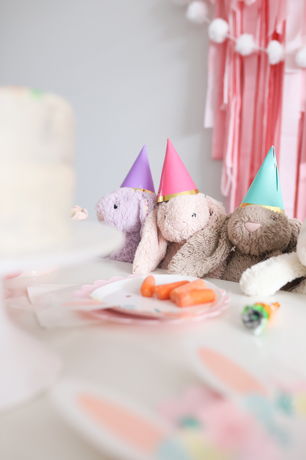 Pink and purple bunny stuffed animals wearing party hats at a Easter birthday celebration.