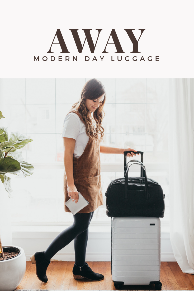 Girl standing with some white luggage and a black carry on bag ready for holidays.