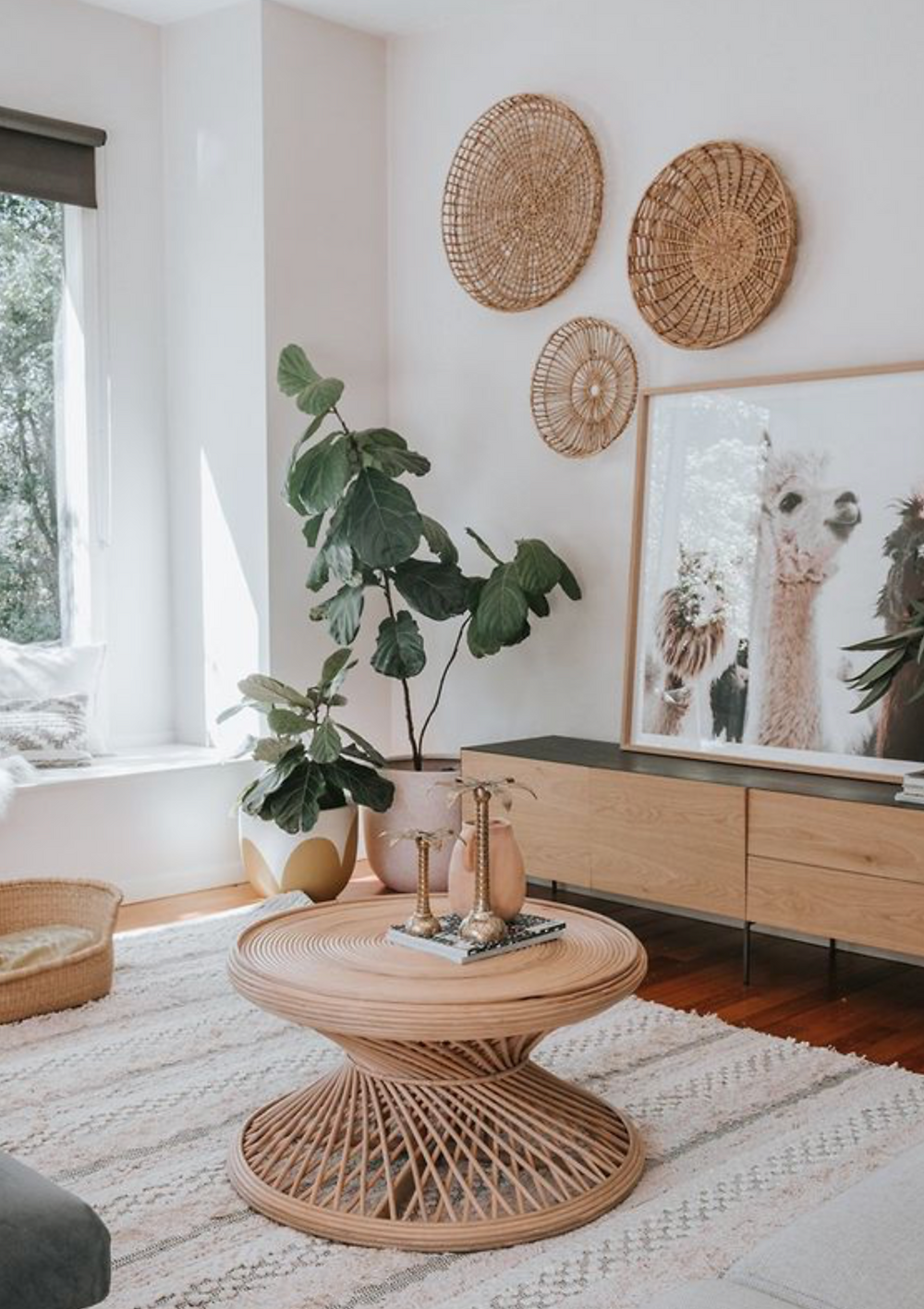 A living room with some vintage baskets hanging on the wall, a wool cream rug on. the floor and some natural wood tables.