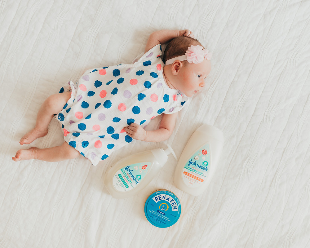 Newborn baby laying on the bed next to some Johnson's bath time products.