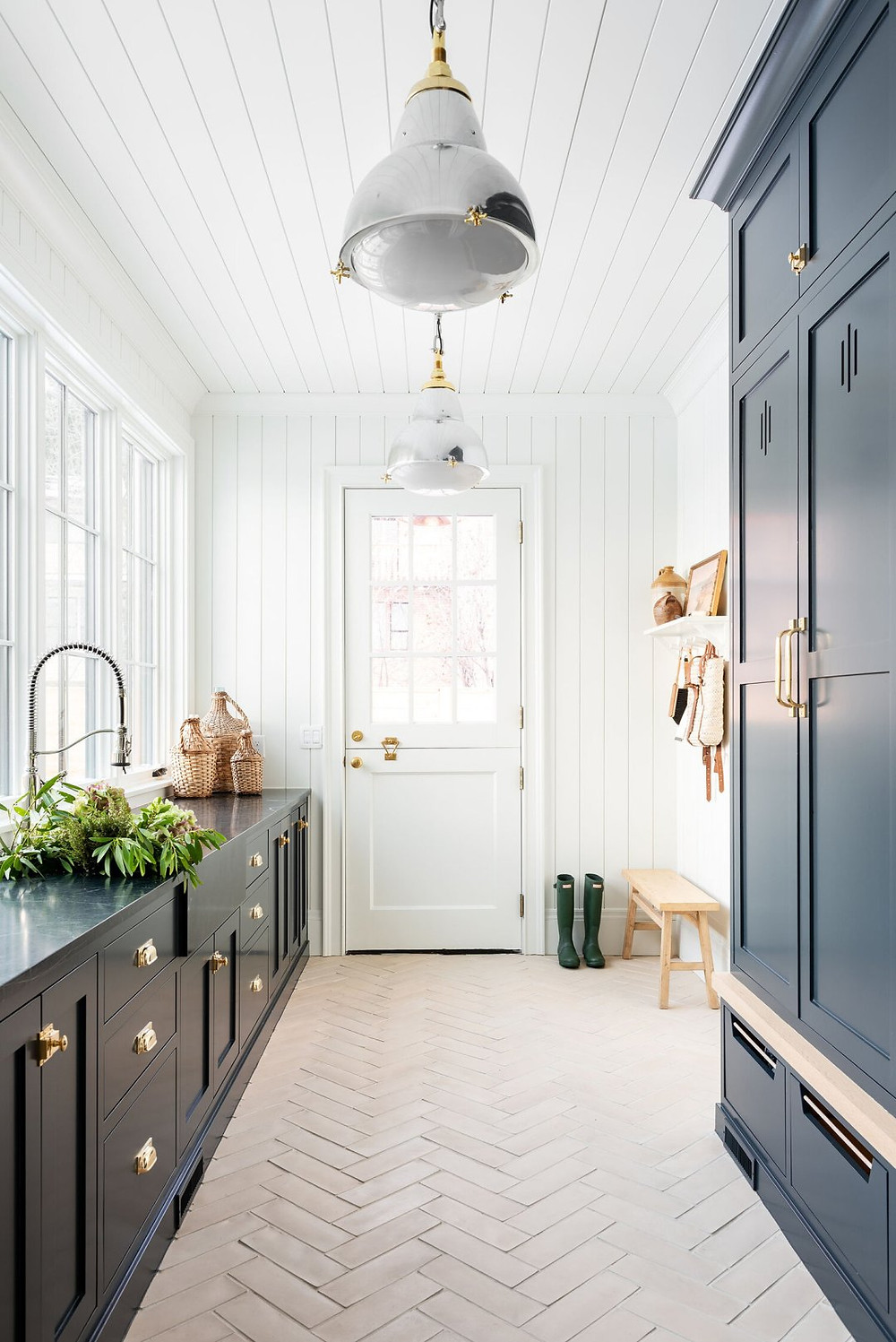 navy blue cabinets dark stone counter herringbone brick tile dutch door polished chrome and brass pendant lights shiplap ceiling and shiplap walls  wood bench hunter rain boots wall hooks