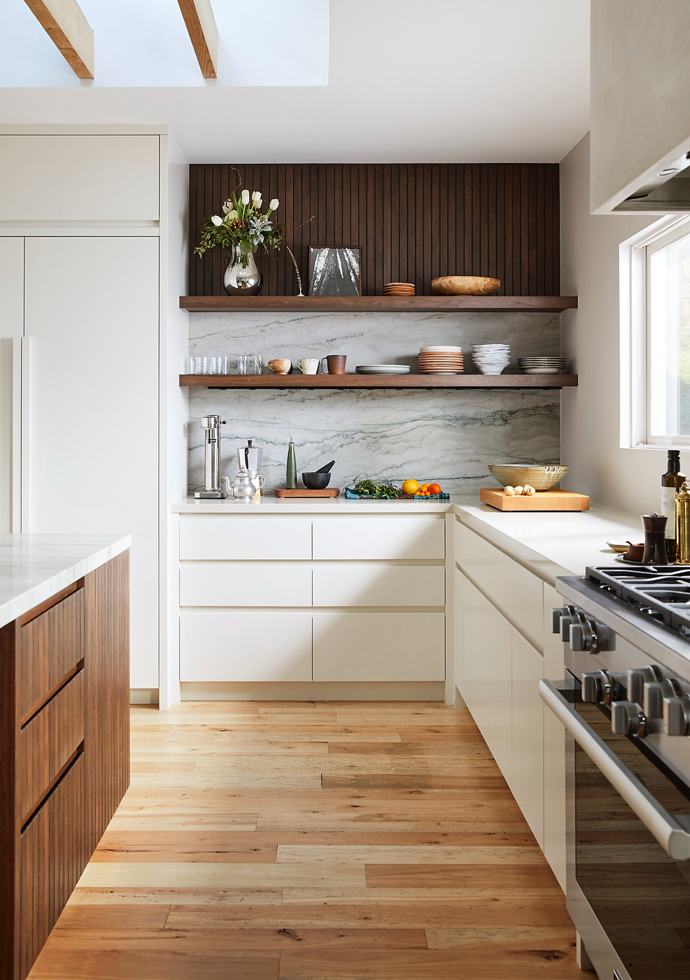 A modern white kitchen with walnut open shelves beautifully styled with dishes and vases.