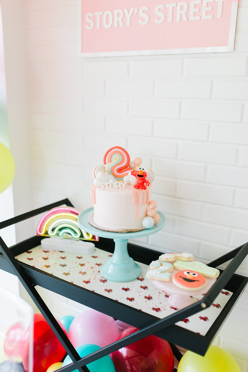 An Elmo Birthday party with colourful balloons, pink Elmo birthday cake and Elmo cookies on a black cart.