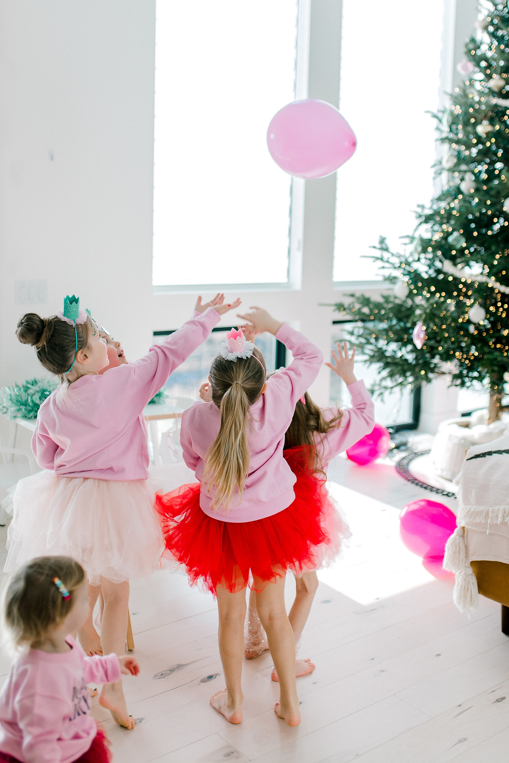 Sugarplum fairy gang plays in their pink, white and red tutu's while playing with pink balloons in front of a lit Christmas tree.