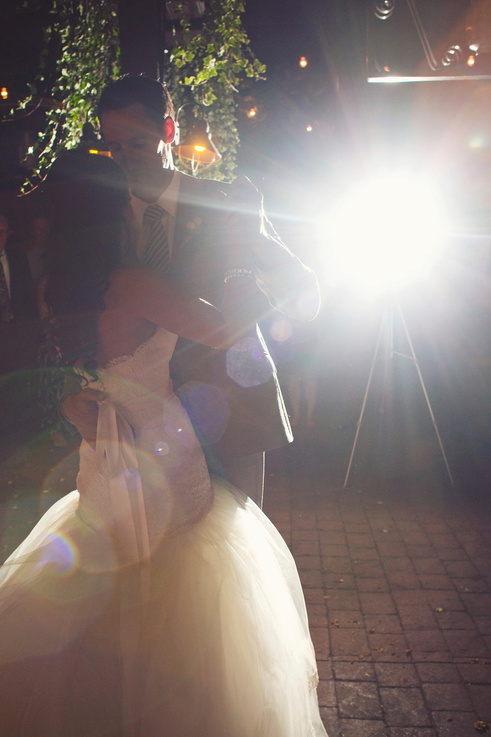 A bride and groom dance together beneath the stars as guests watch.