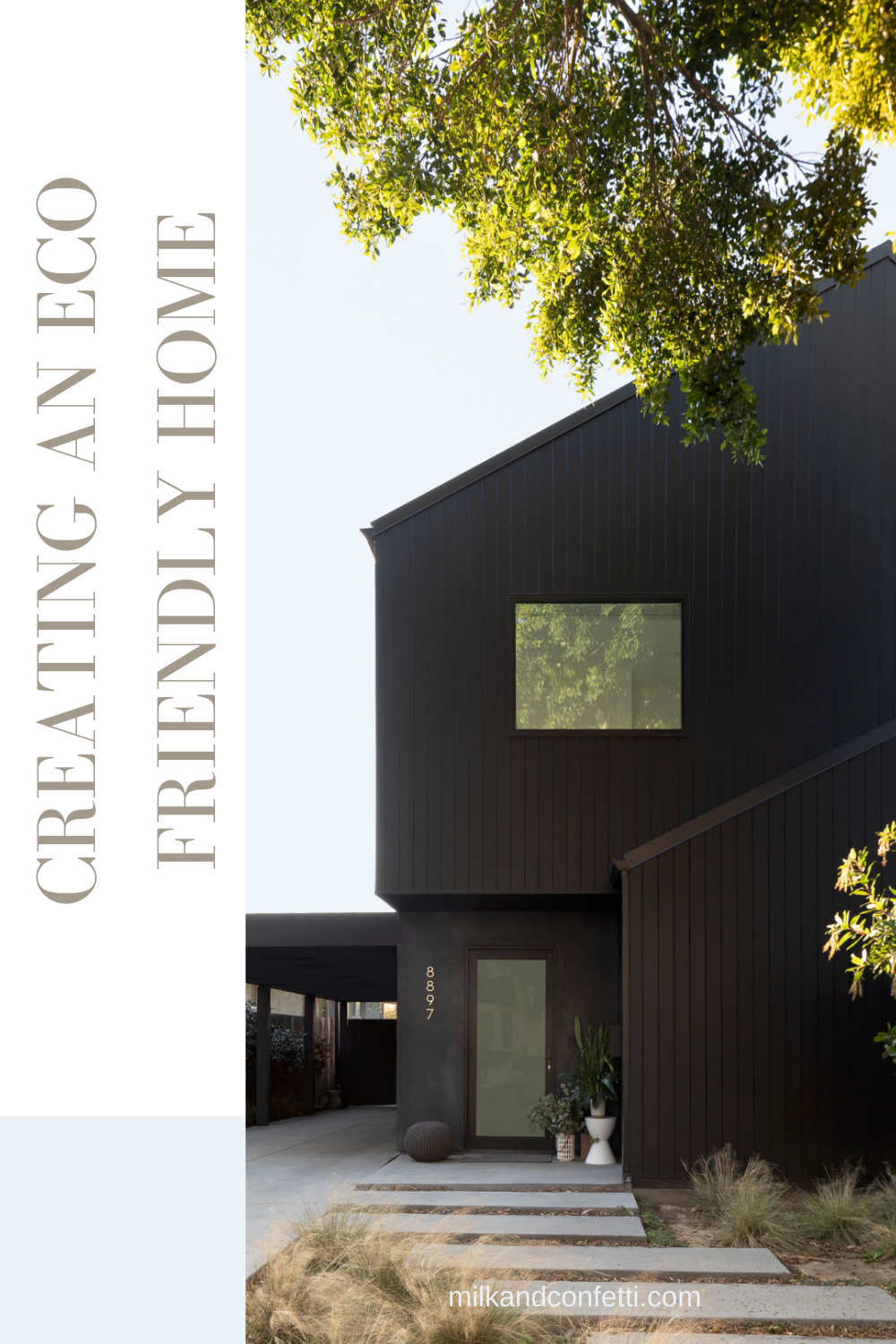 A modern minimal home with a black exterior with a modern concrete slab sidewalk and tall trees.