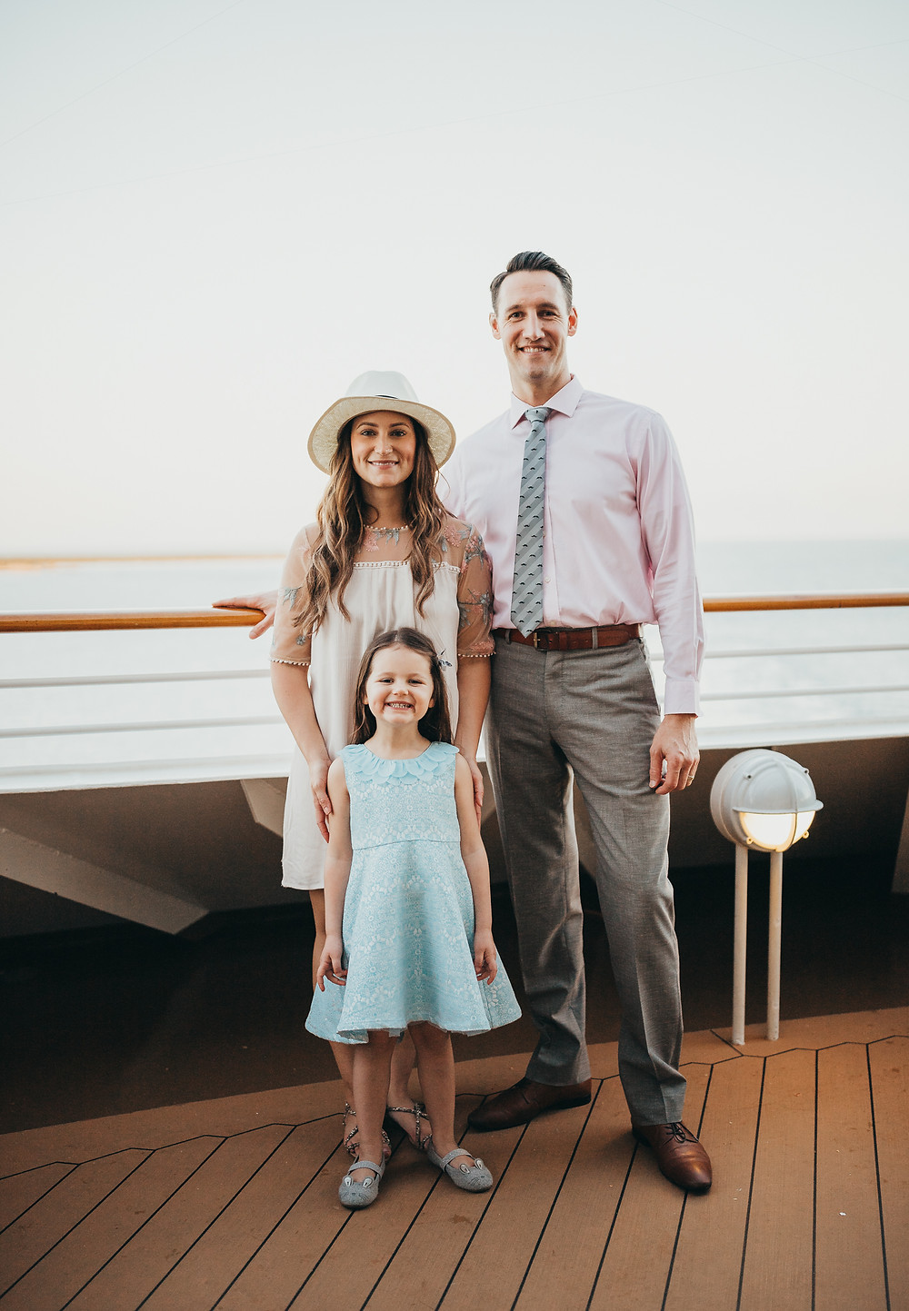 A family of three dressed up nicely on a cruise ship deck.