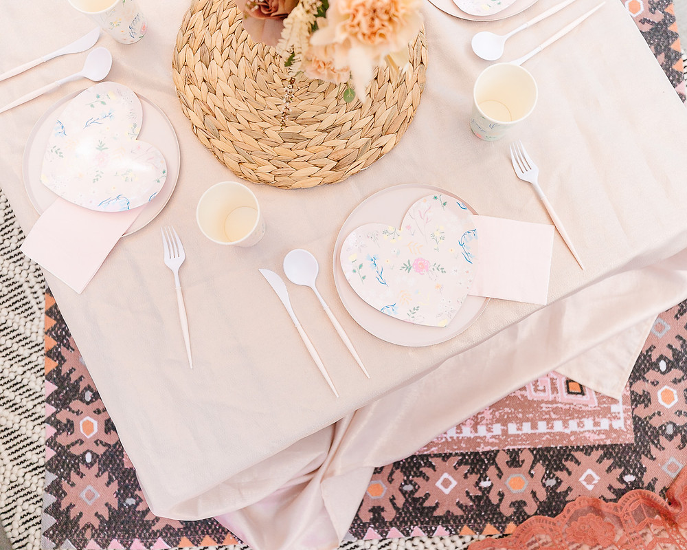 A table set for a birthday party with pink linens, heart shaped plates and a moroccan rug.