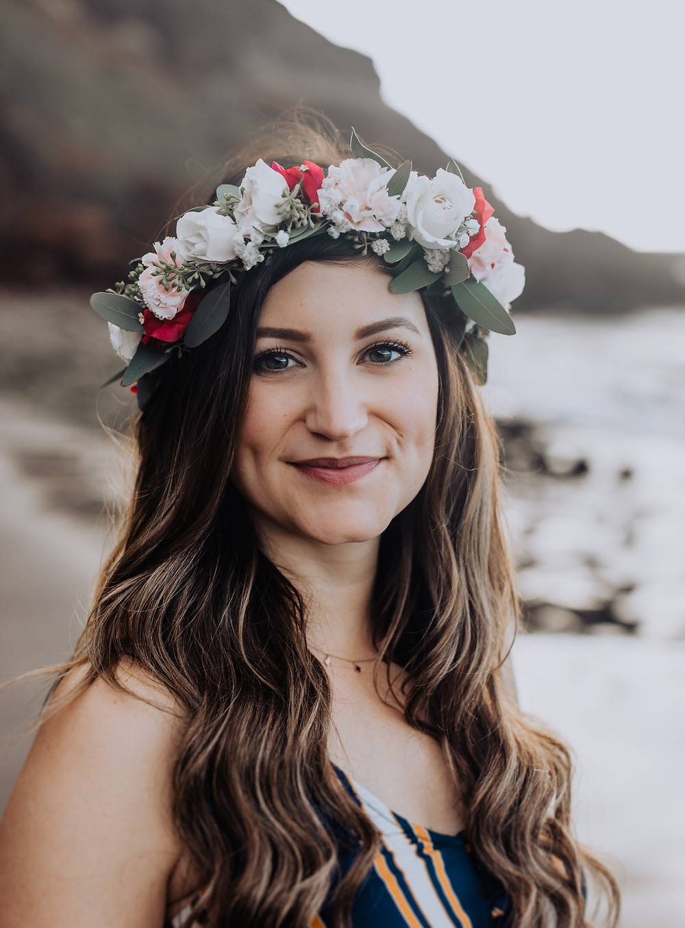 A girl smiles at the camera with a flower lei in her hair.