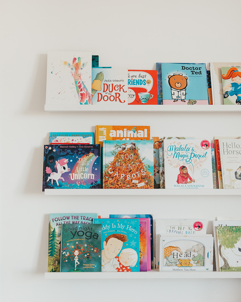 A white wall of white shelves lined with some colourful children's books.