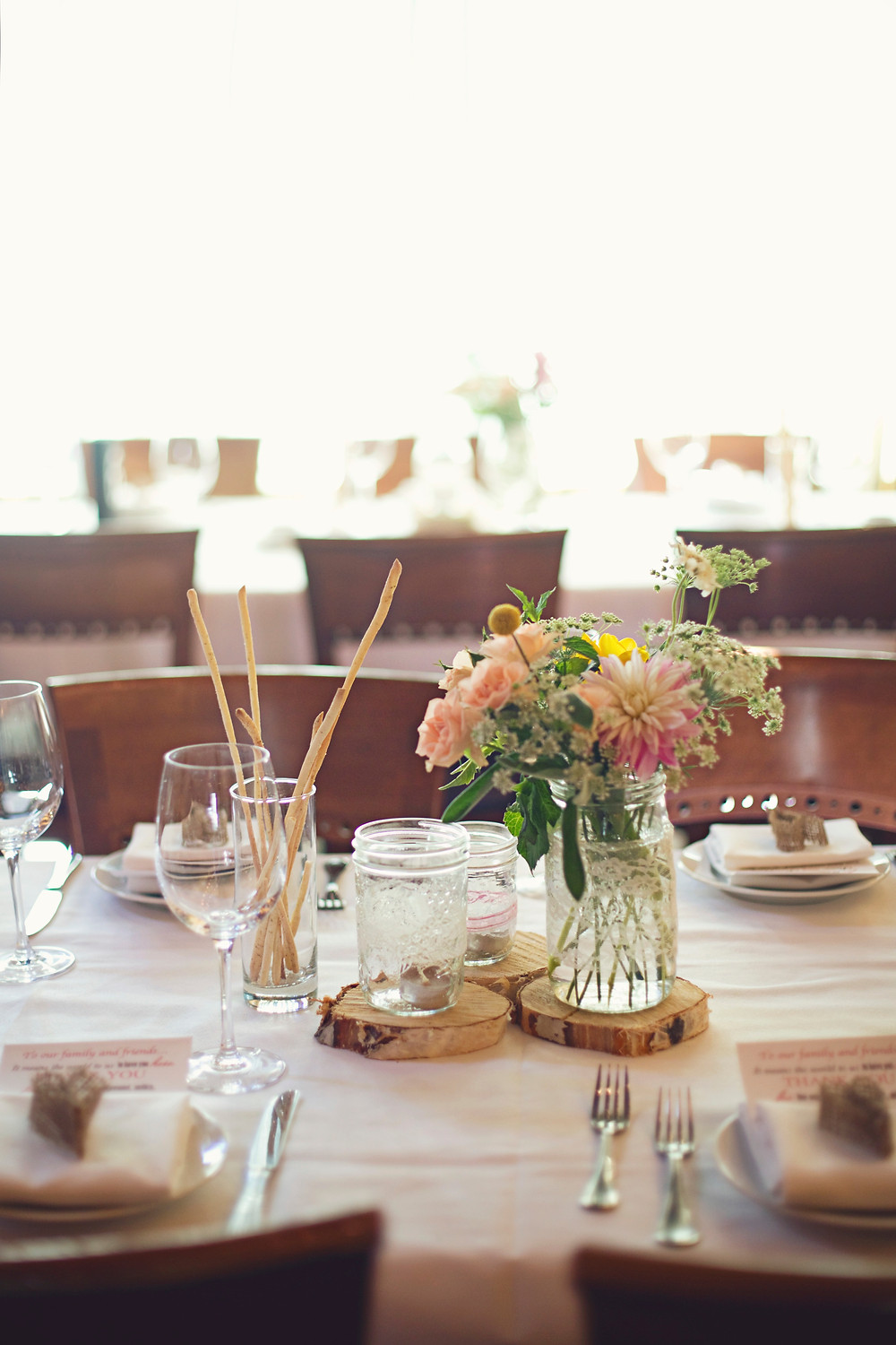 A table elegantly set at a rustic Italian inspired wedding with garden flowers, wooden rounds, and mason jars wrapped with lace.