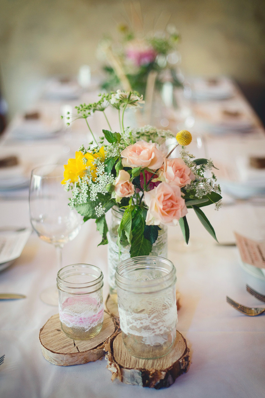 A table set at a rustic Italian inspired wedding with romantic garden flowers, wooden rounds, and mason jars wrapped with lace awaits guests.
