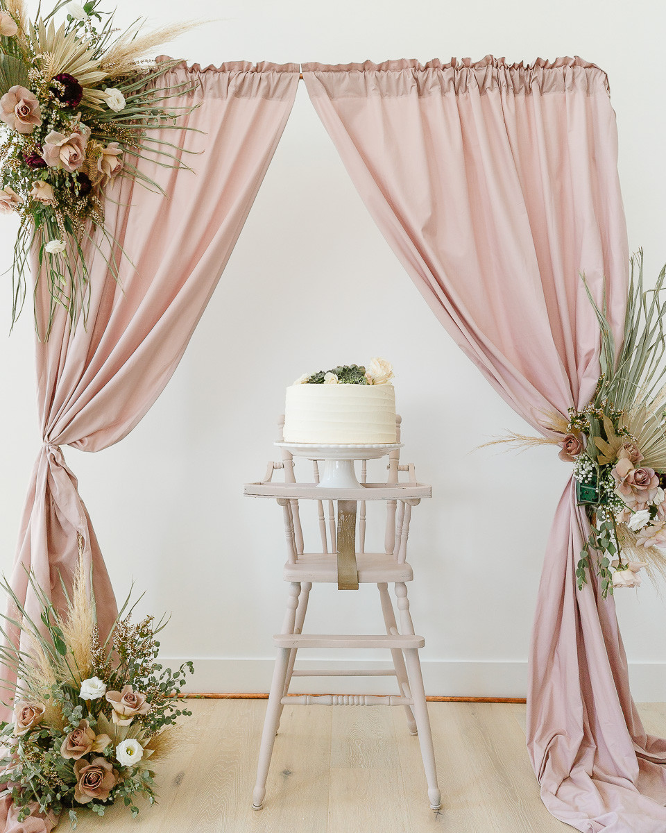 A white cake topped with flowers and succulents is sitting on a pink high chair in front of a floral back drop at a birthday party.