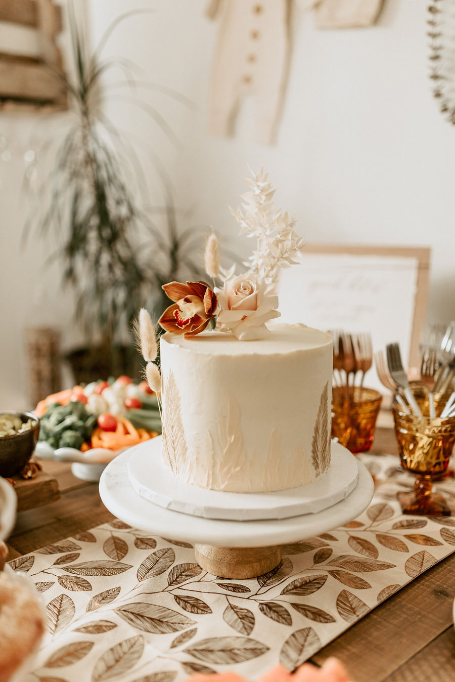 A white cake decorated at a boho romantic inspired baby shower is decorated with flowers, grasses and bunny tails.