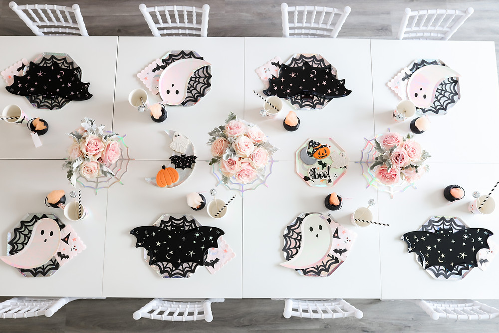 A kid's halloween themed party showcased around a white table with pink roses and white ghosts, black bats, kids cups and paper plates next to ghosts, and pumpkins wearing witches hats.