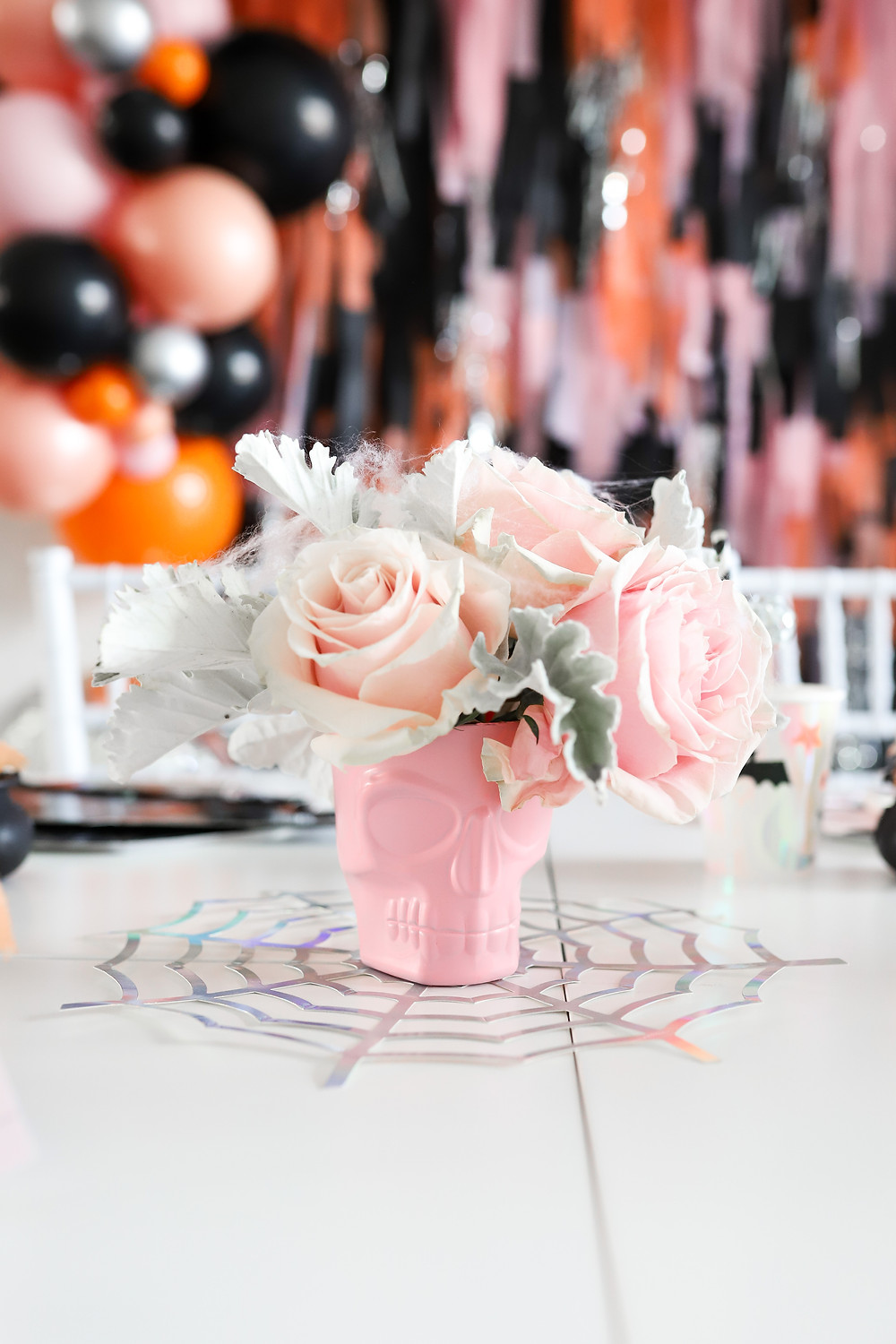 A wall filled with black, orange, pink, sparkly arched balloons and streamers for a children's halloween party filled with decorations on a white kids table with a pink skull vase holding pink roses covered in cobwebs.