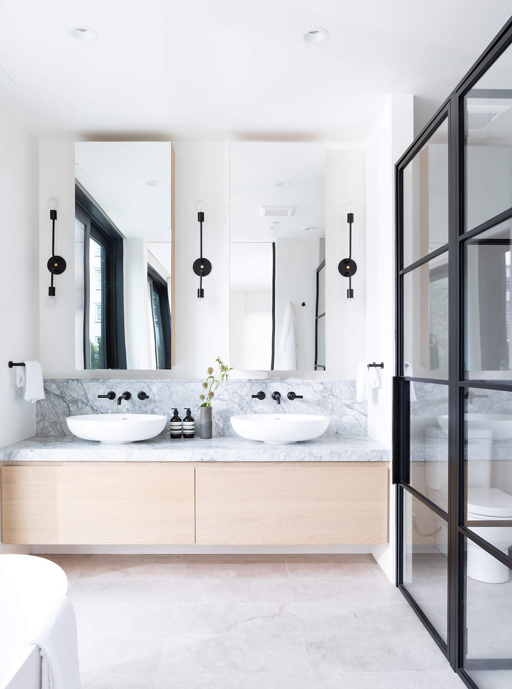 A modern bathroom with black accents, light wood cabinets, marble countertops and rectangular mirrors.