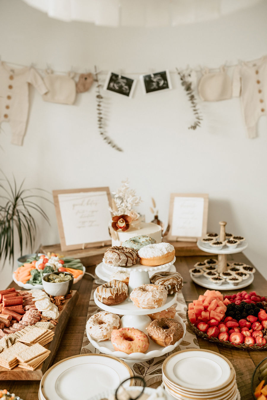 A beautifully styled table of food is displayed at a boho floral vintage baby shower with lace and floral details.