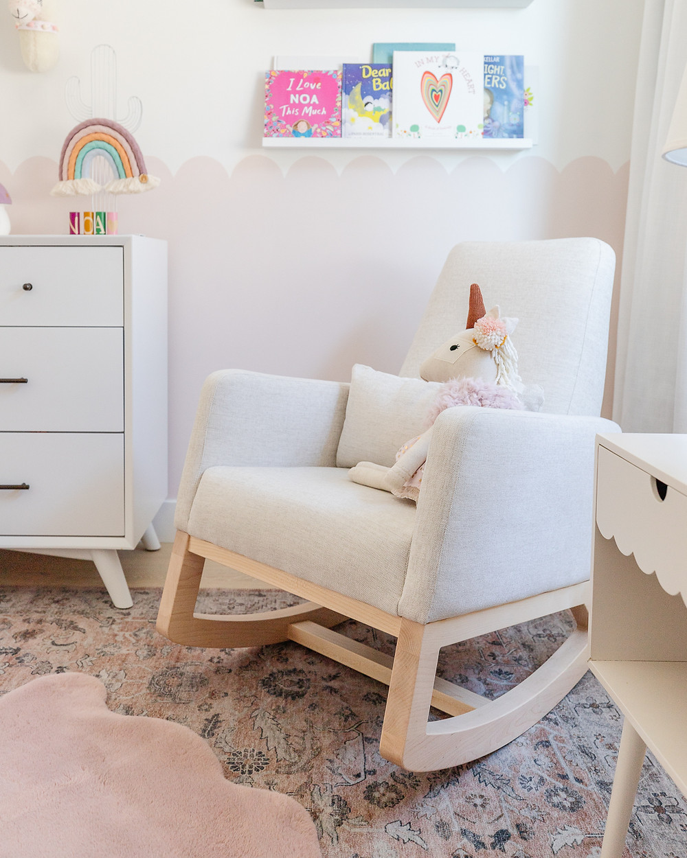 A boho modern baby girls nursery with llama and cactus wallpaper, a blush pink rug, a white rocking chair, a beaded light pendant, a white crib and a scalloped pink wall behind white drapery.