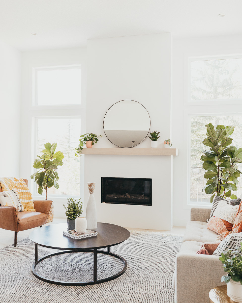 A bright living room with white walls and a large area rug with mid century furniture in front of a modern linear fireplace with a white oak mantle.