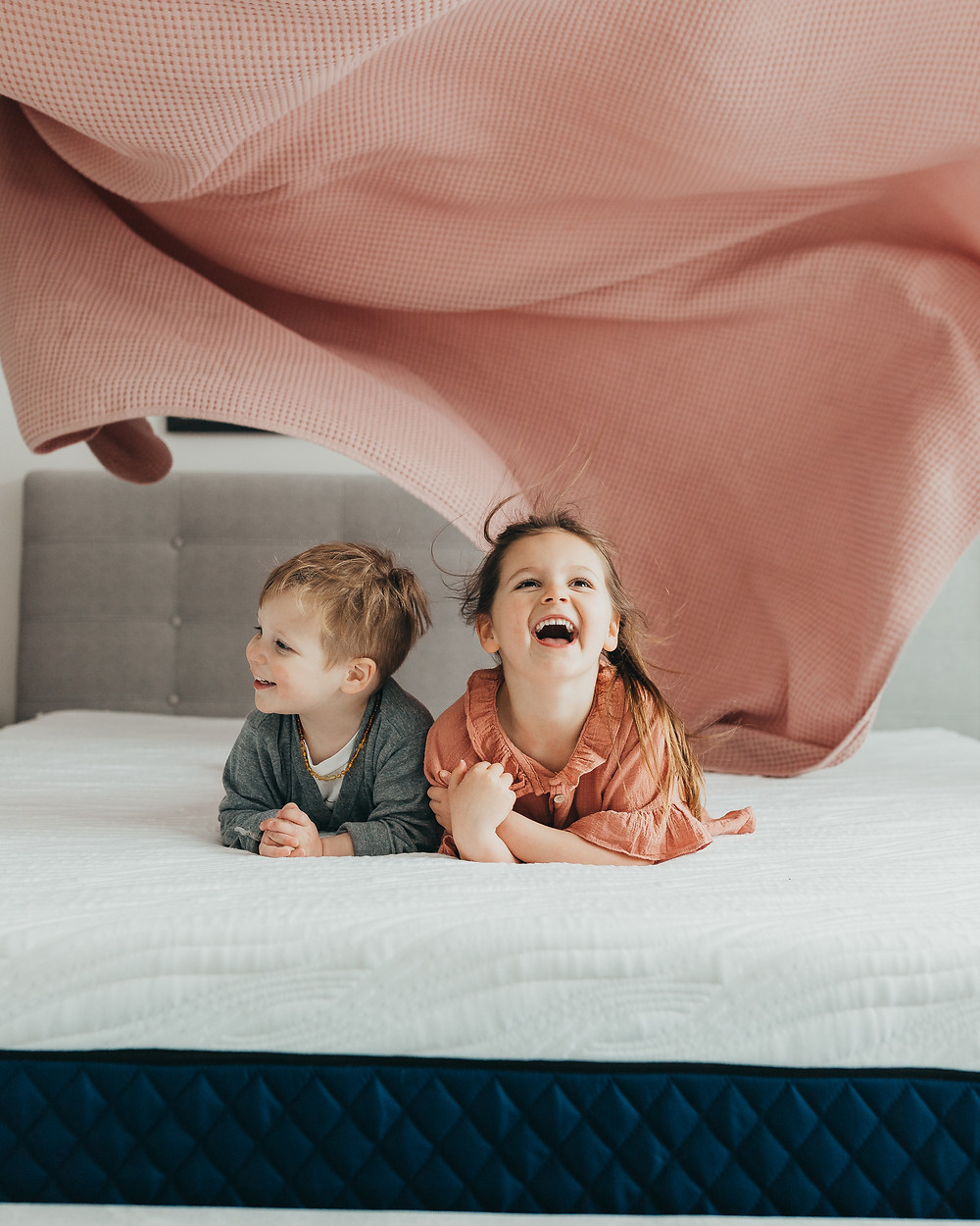 A little girl and boy laughing on the bed as a blanket is lifted above their heads while they lay on a silk and snow mattress.