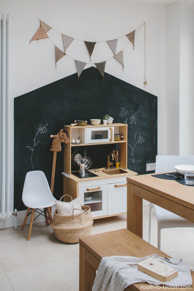 A beautiful chalk board paint wall in neutral childrens playroom with simple wall art and a childrens IKEA play kitchen