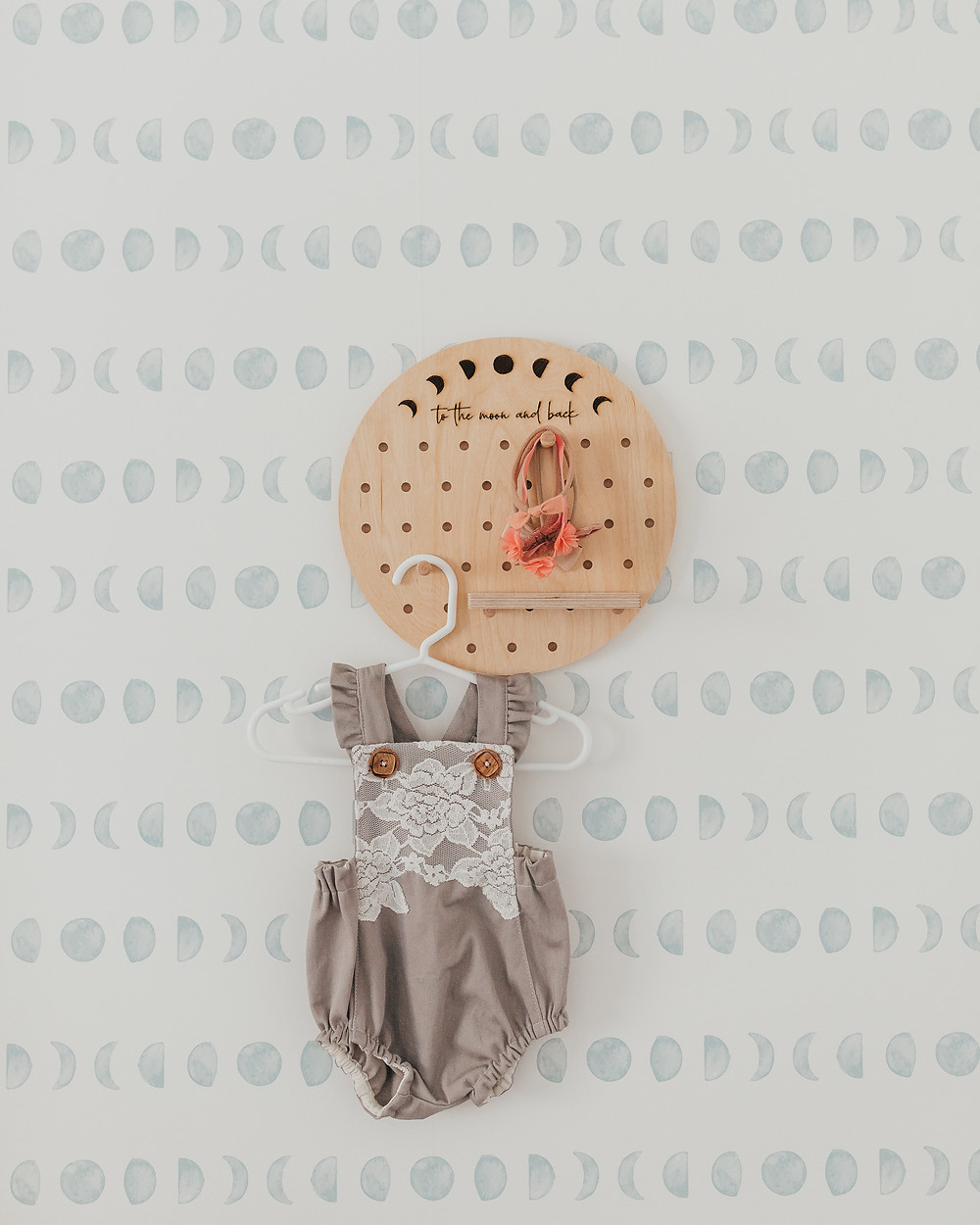 A baby romper hanging from a wooden peg board in a nursery.