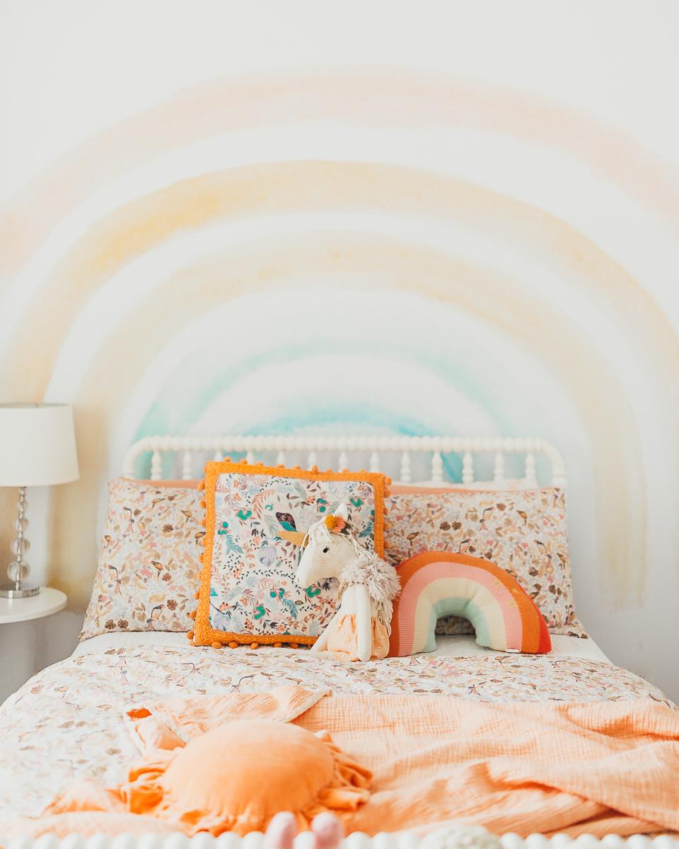 A little girl's rainbow themed bedroom .