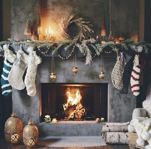A grey concrete Christmas holiday fireplace with a mantel decorated with greenery, bottle brush trees, a wreath and stockings for a stylish and moody look.