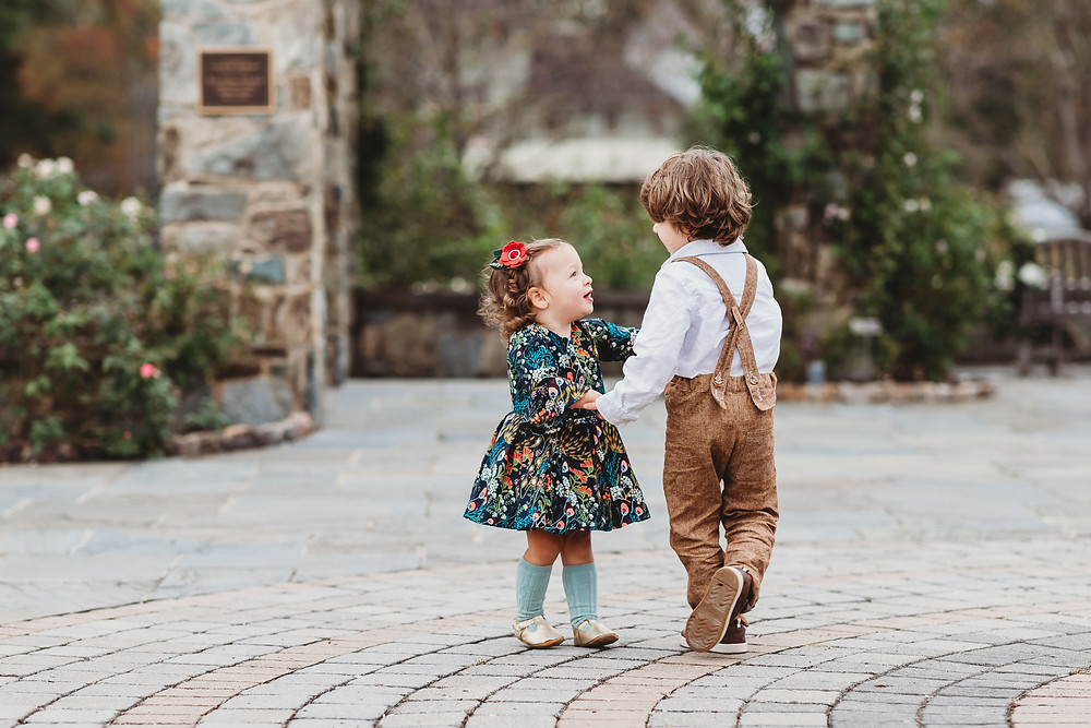 A little boy and girl dancing together outside on a cobble stone street.