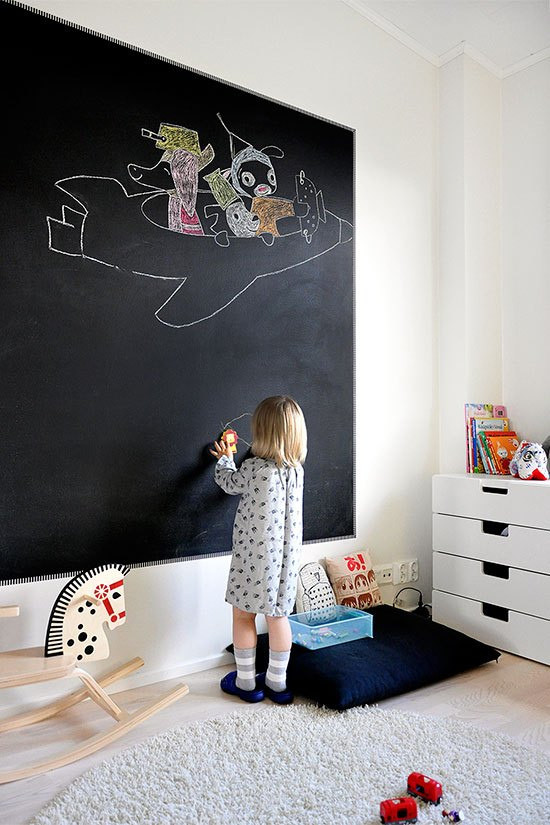 A black chalk board wall in a childrens bedroom with light hardwood floors and neutral area rug with a white dresser