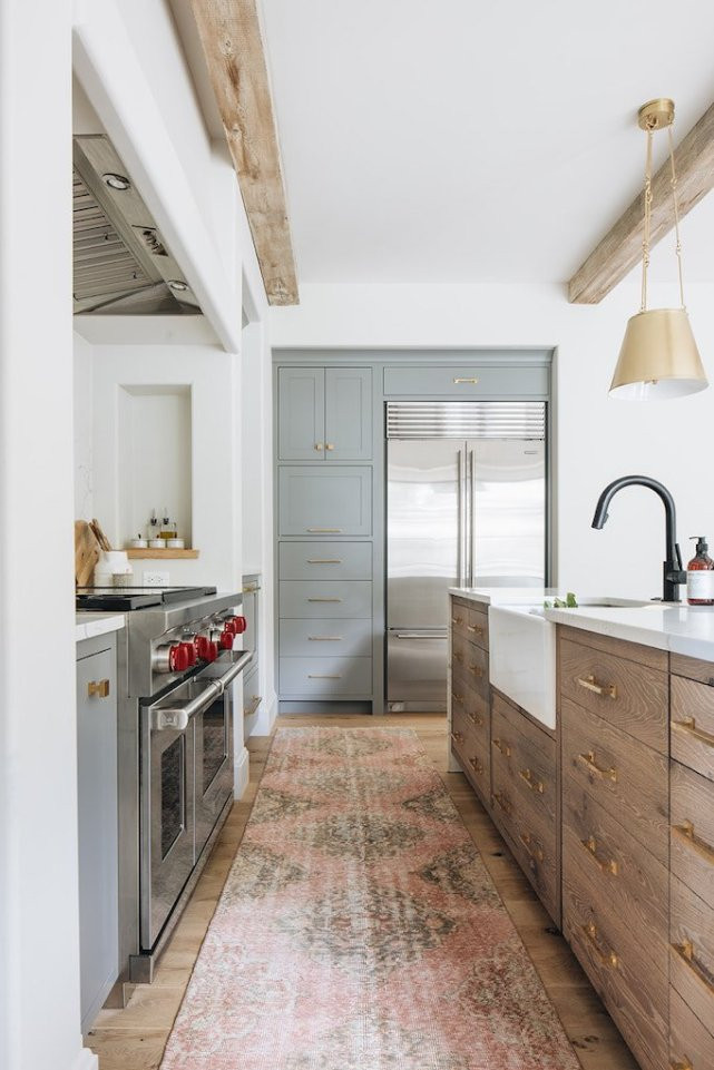 exposed wood beam kitchen wood island cabinets two tone grey perimeter cabinets wolf over black hardware built in fridge brass pendant lights pink and brown runner