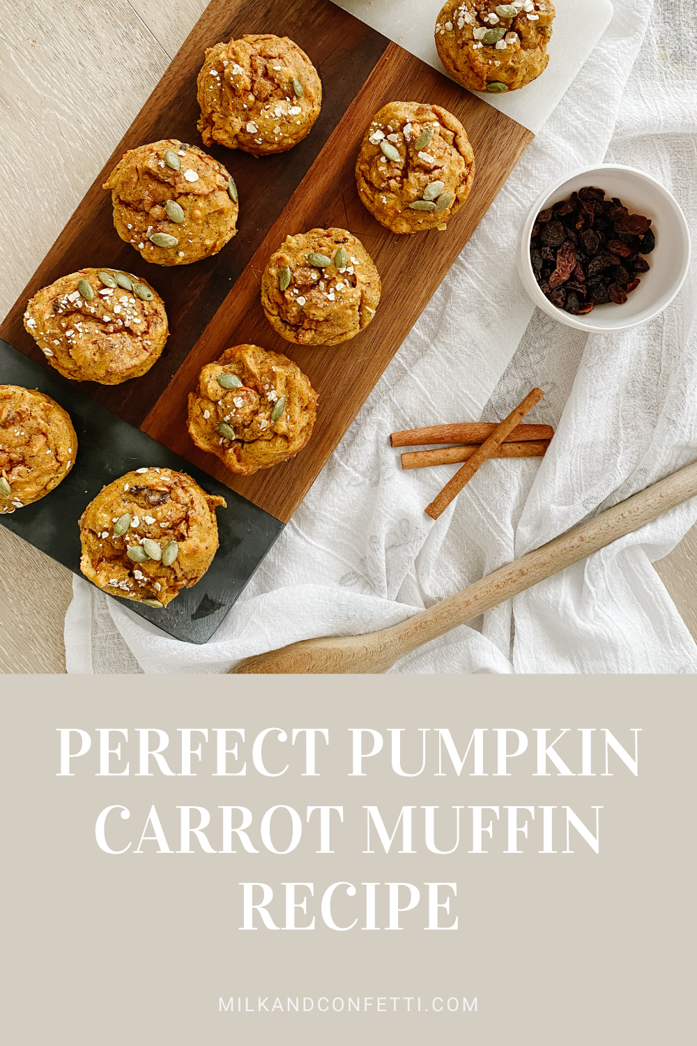 A wooden platter on a white table cloth shows off pumpkin and nut muffins beside cinnamon sticks, a bowl of raisins and a wooden spoon.