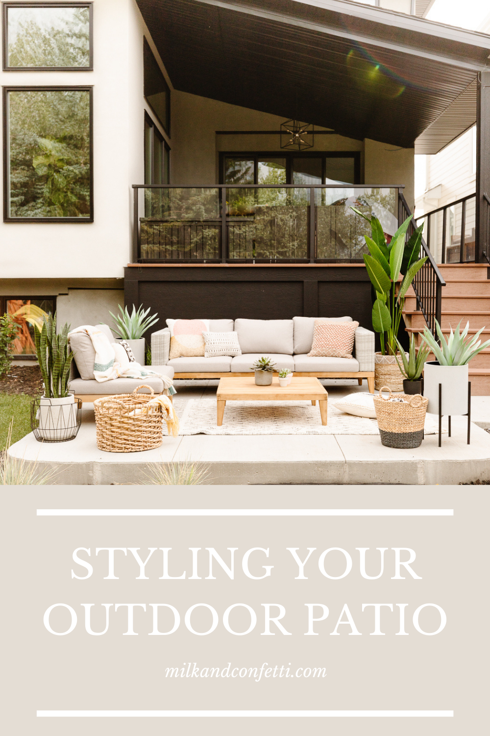 Outdoor patio wood fence with string lights neutral wicker sofa wood legs with beige fabric patterned throw cushions beige and black area rug teak coffee table with succulent pots black metal pot stand with aloe plant chair with striped throw blanket