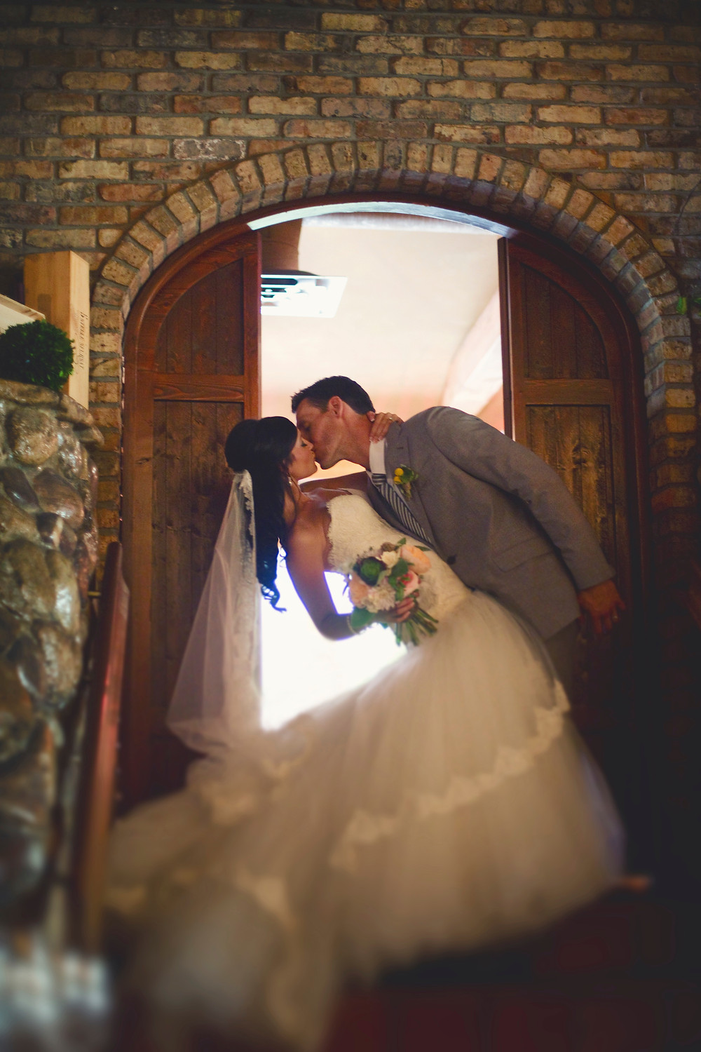 A bride in a lace and tulle Lazaro wedding dress is kissing her groom in his light grey suit beneath a brick archway in a rustic Italian restaurant.