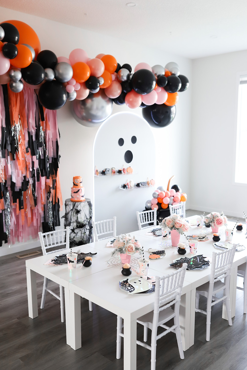 A giant arch of orange, black, pink, metallic silver balloons and streamers hanging on the wall in front of a kids white table decorated with pink roses, a bat themed cake, kids cups, tiny pumpkins, cauldrons, ghosts, and scary party aesthetics at a Halloween party.