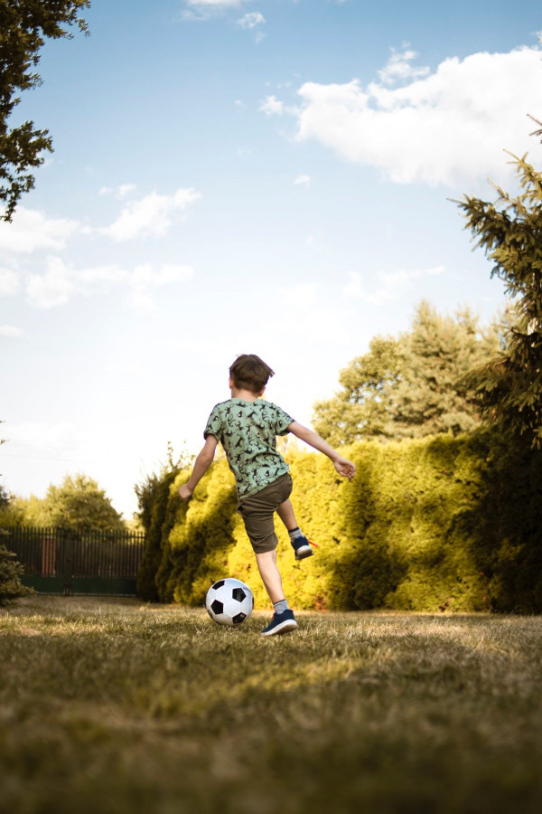 A young boy playing soccer in the park.