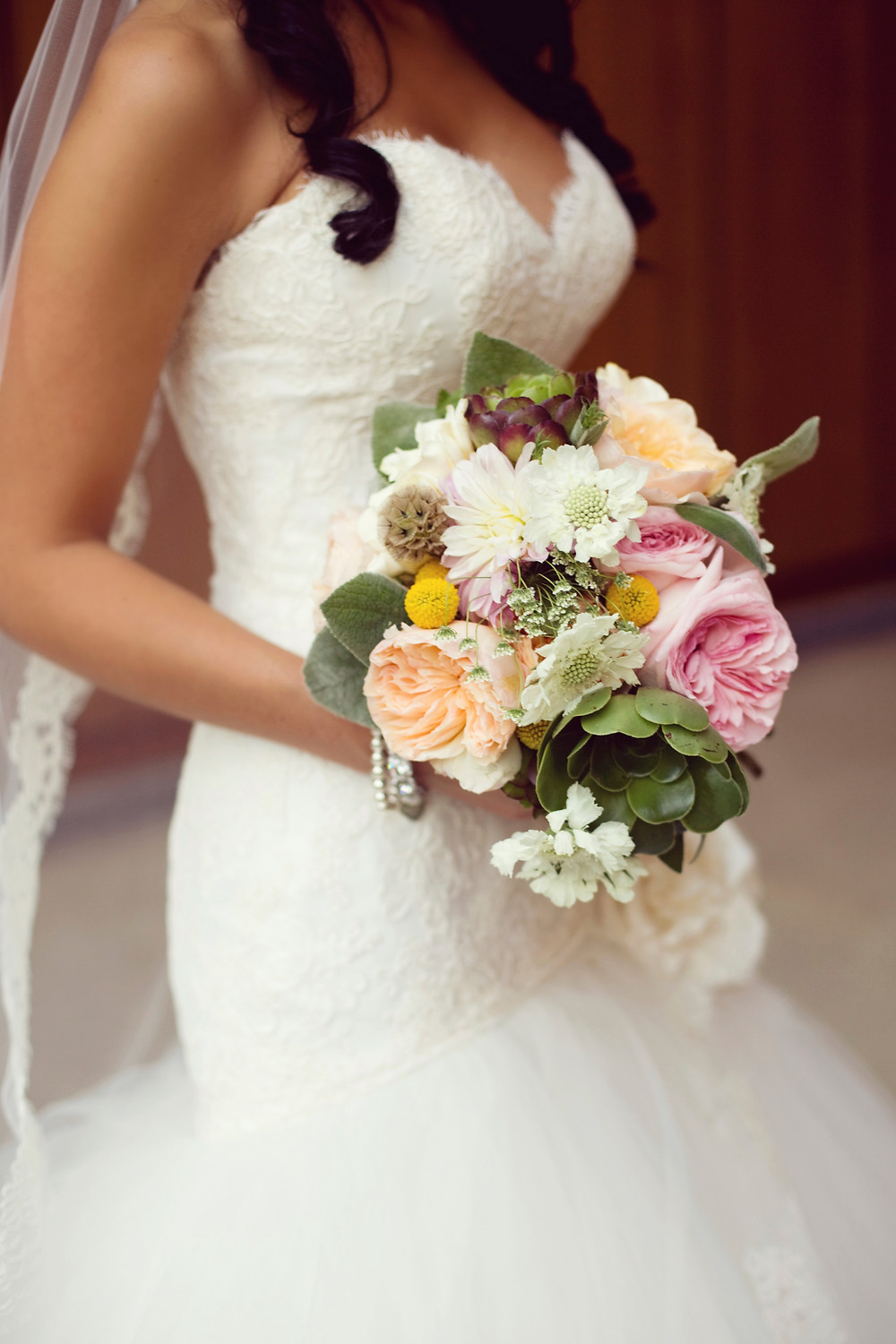 A bride wearing a lace Lazaro wedding dress is holding a large bouquet of romantic garden flowers on her wedding day.