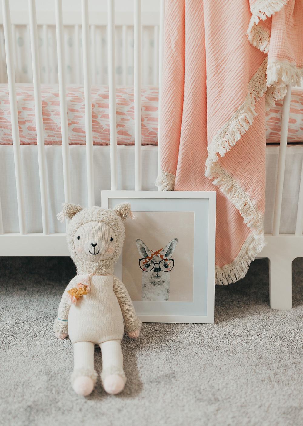 A cuddle and kind llama doll next to a llama print in a nursery.