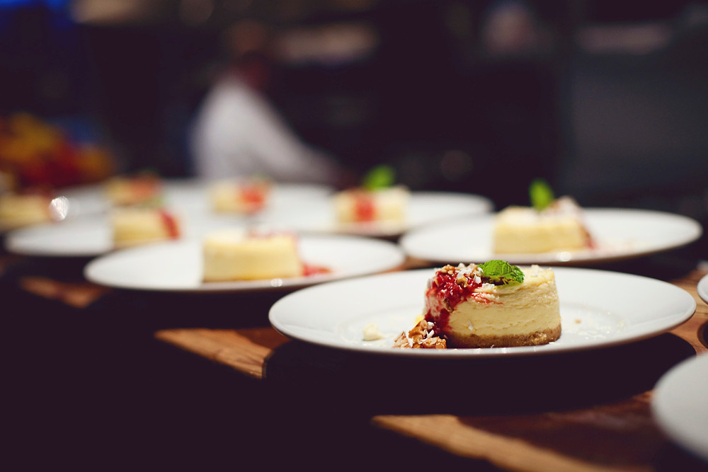 A delicious Italian white chocolate cheese cake plated on white plates with a spring of mint at a wedding dinner.