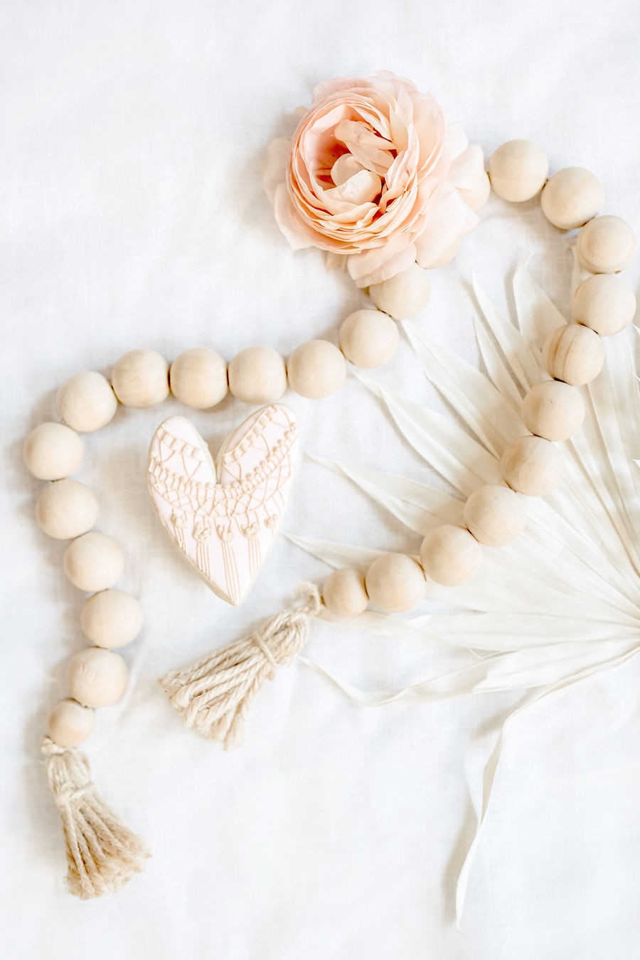 A delicious delicate decorated heart shaped cookie at a boho inspired baby shower next to a wooden string of beads for decor.