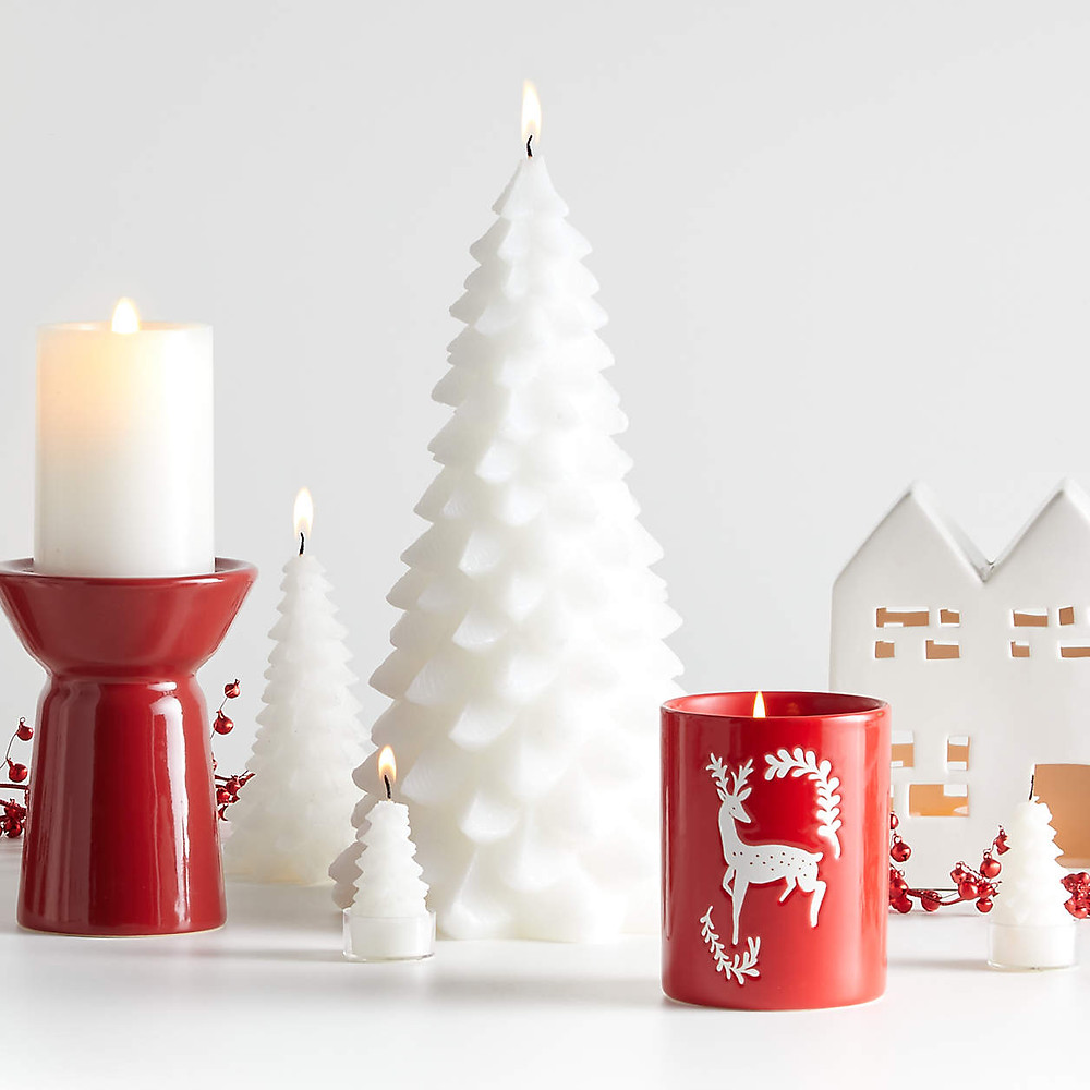 Scandinavian style Christmas decor in red and white colors is set up for the holidays with candles, Christmas trees, and red ornaments.