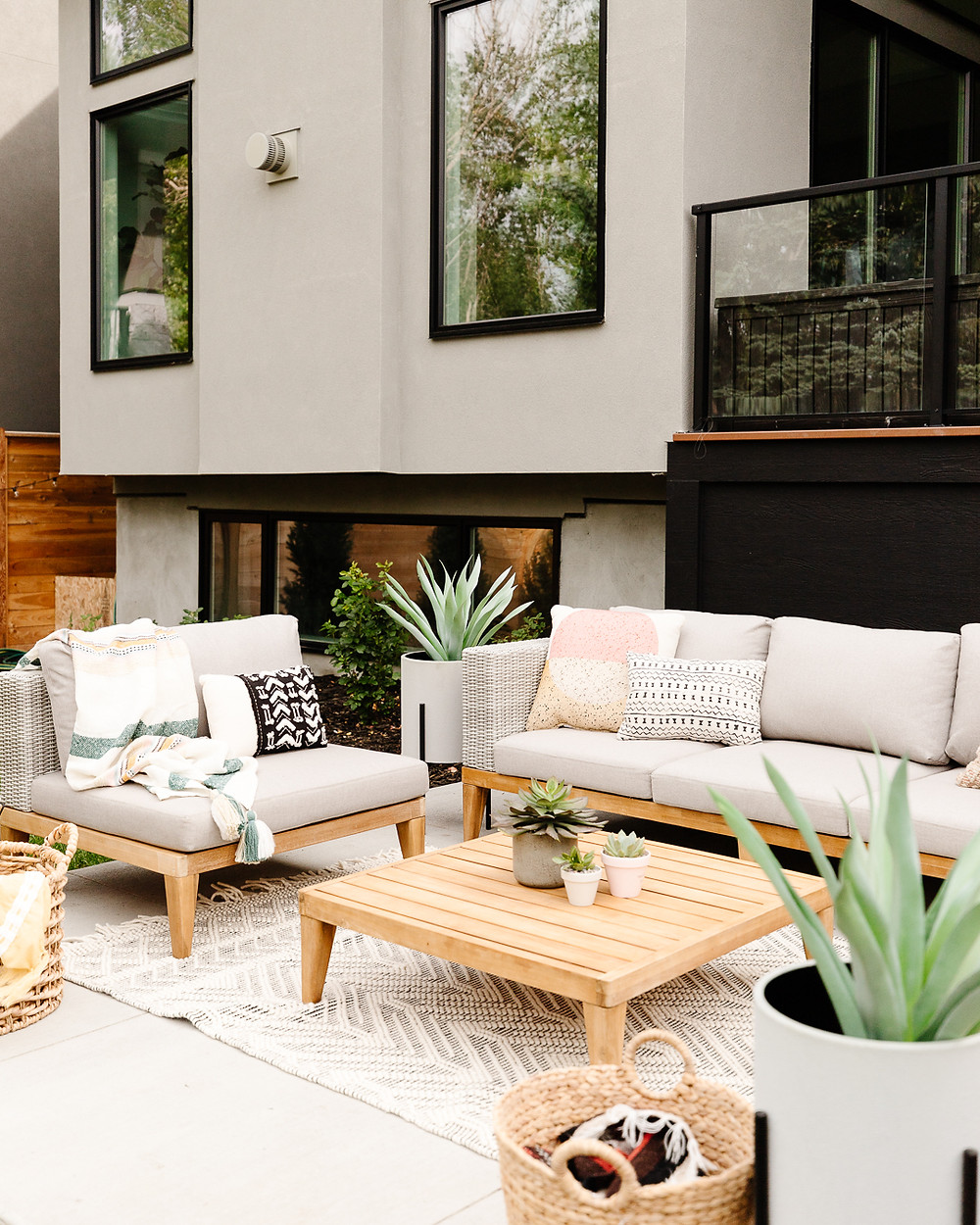 Modern outdoor wicker sofa with wood accents and beige cushions black and white area rug chair with wood accent and striped throw blanket wood accent table with succulent pots wicker basket with blankets patterned accent pillows potted succulents plant backyard concrete patio stucco exterior with black windows raised deck with glass railing