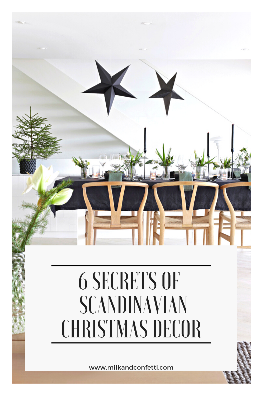 A scandinavian nordic inspired dining room with wishbone wooden chairs, a dining table covered with a black table cloth, black star lights, candles and greenery set up with minimal and modern decor for the Christmas holidays.