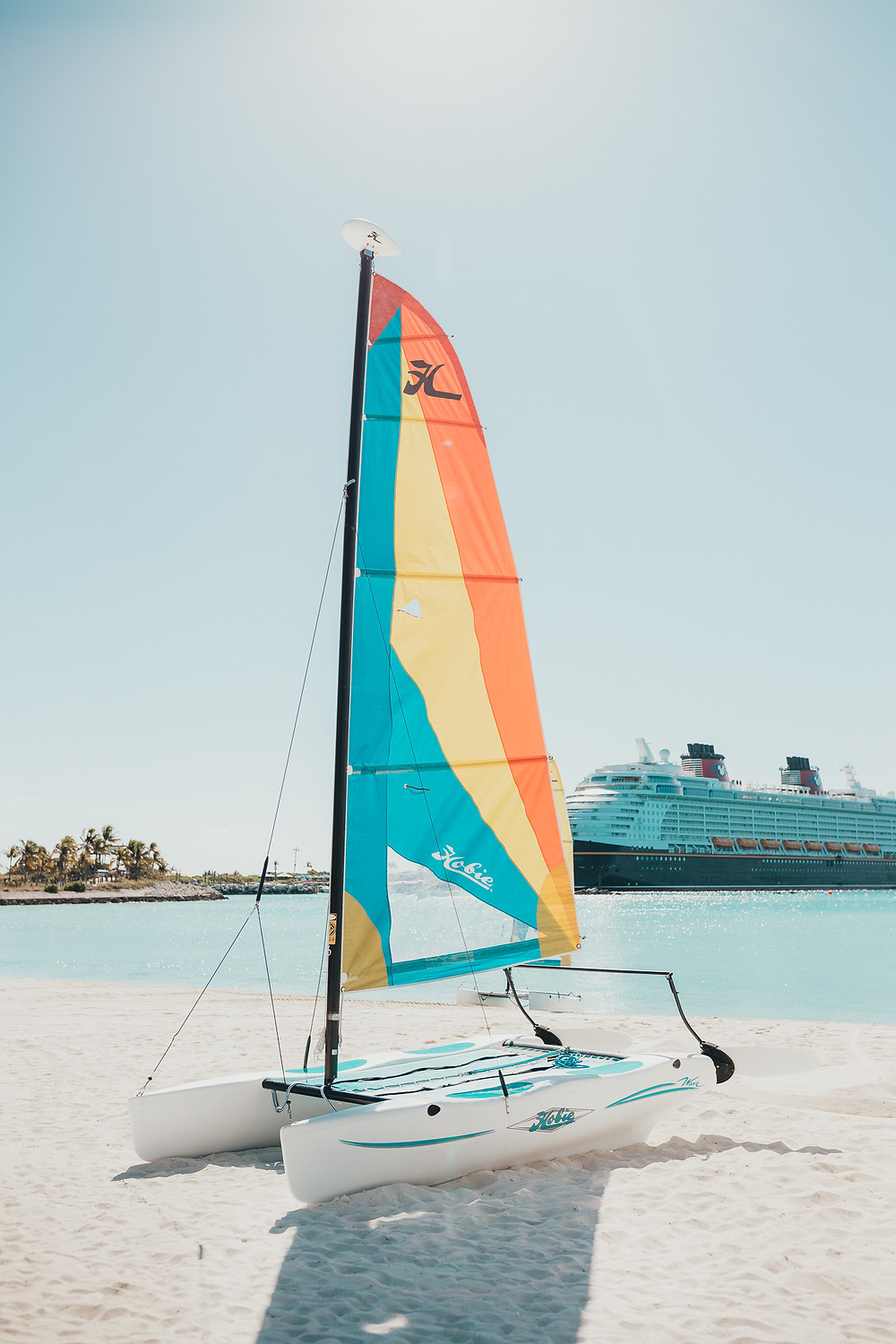 A colourful sail boat in the sand.
