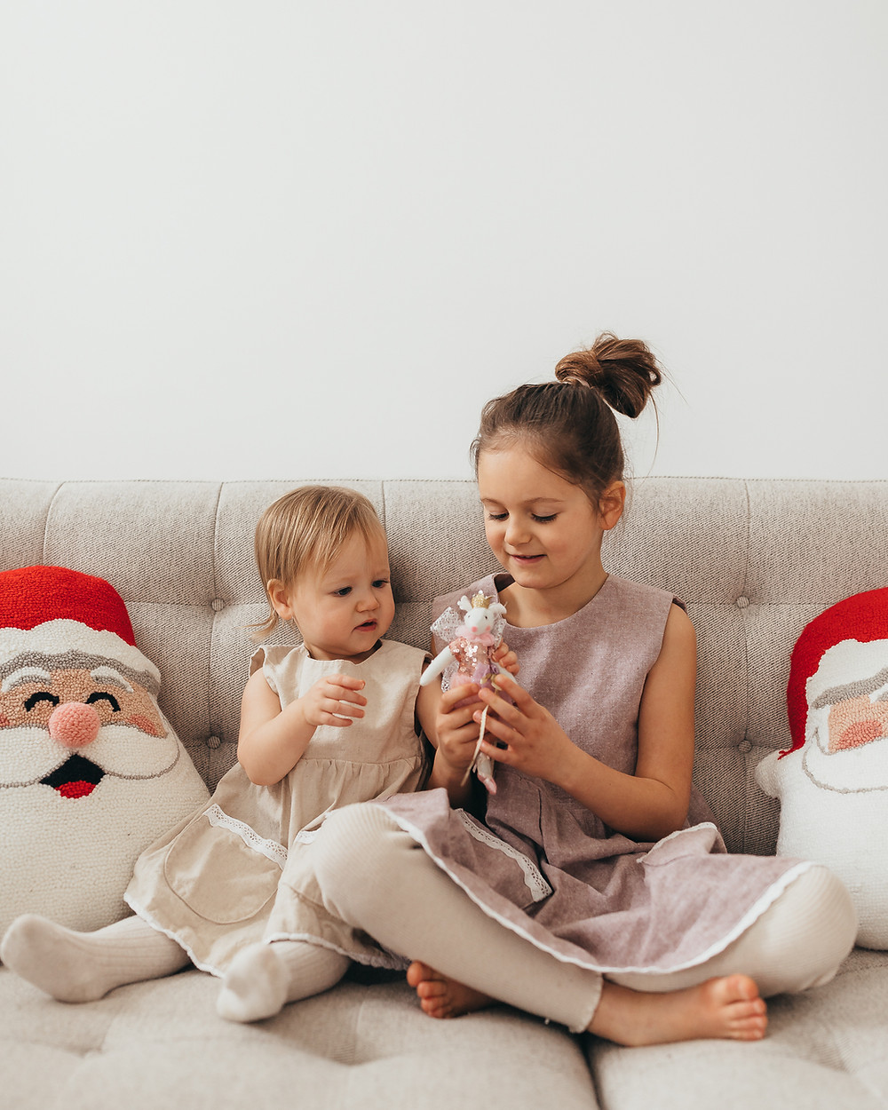 Two little girls in dresses at christmas time sitting on the sofa next to some Santa pillows playing with a glittery mouse holiday decoration.