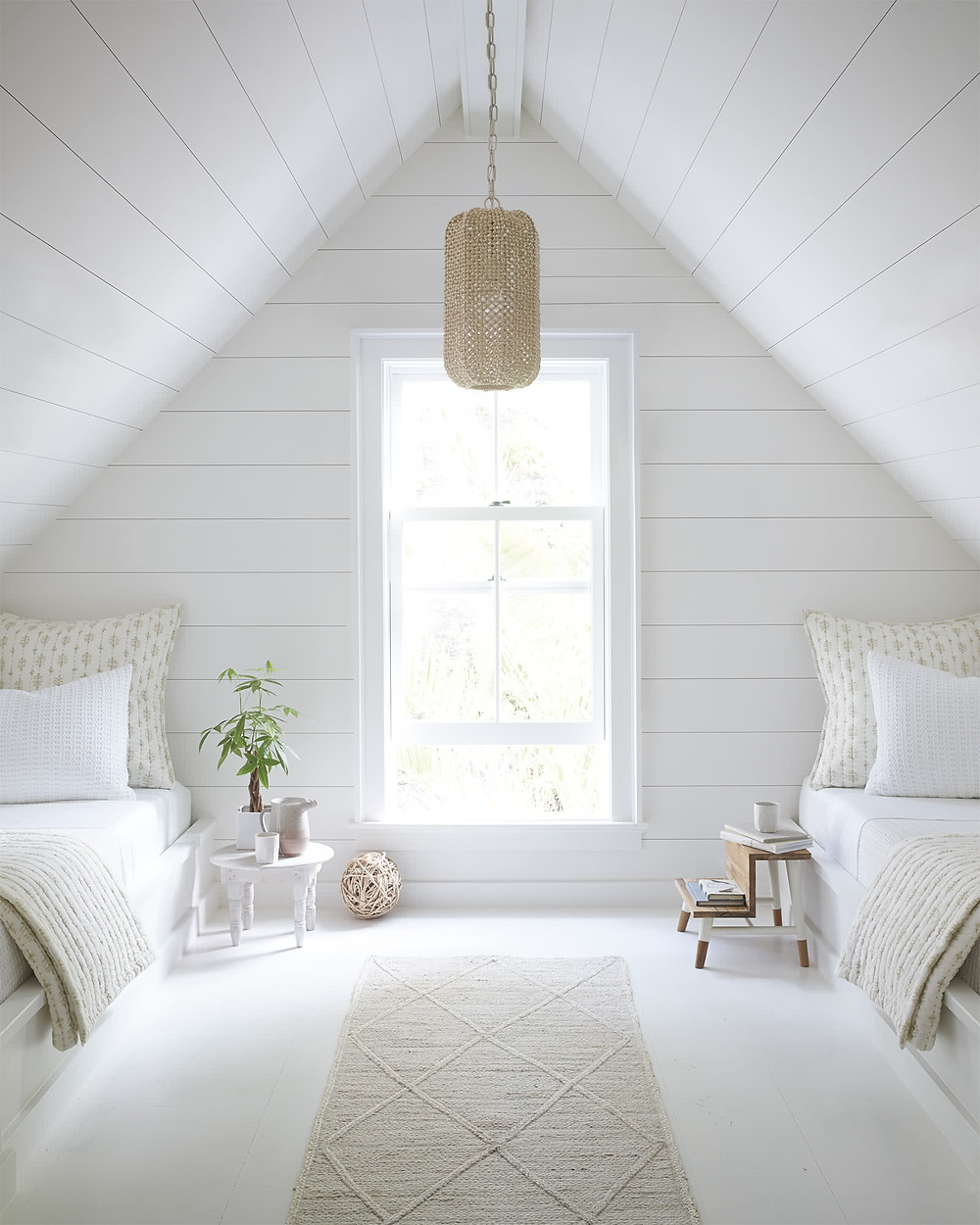 attic bedroom with natural light shiplap walls and vaulted a-frame ceiling two twin beds with wool rug runner natural beige sheets and pillow cases small wood side tables rattan hanging pendant light