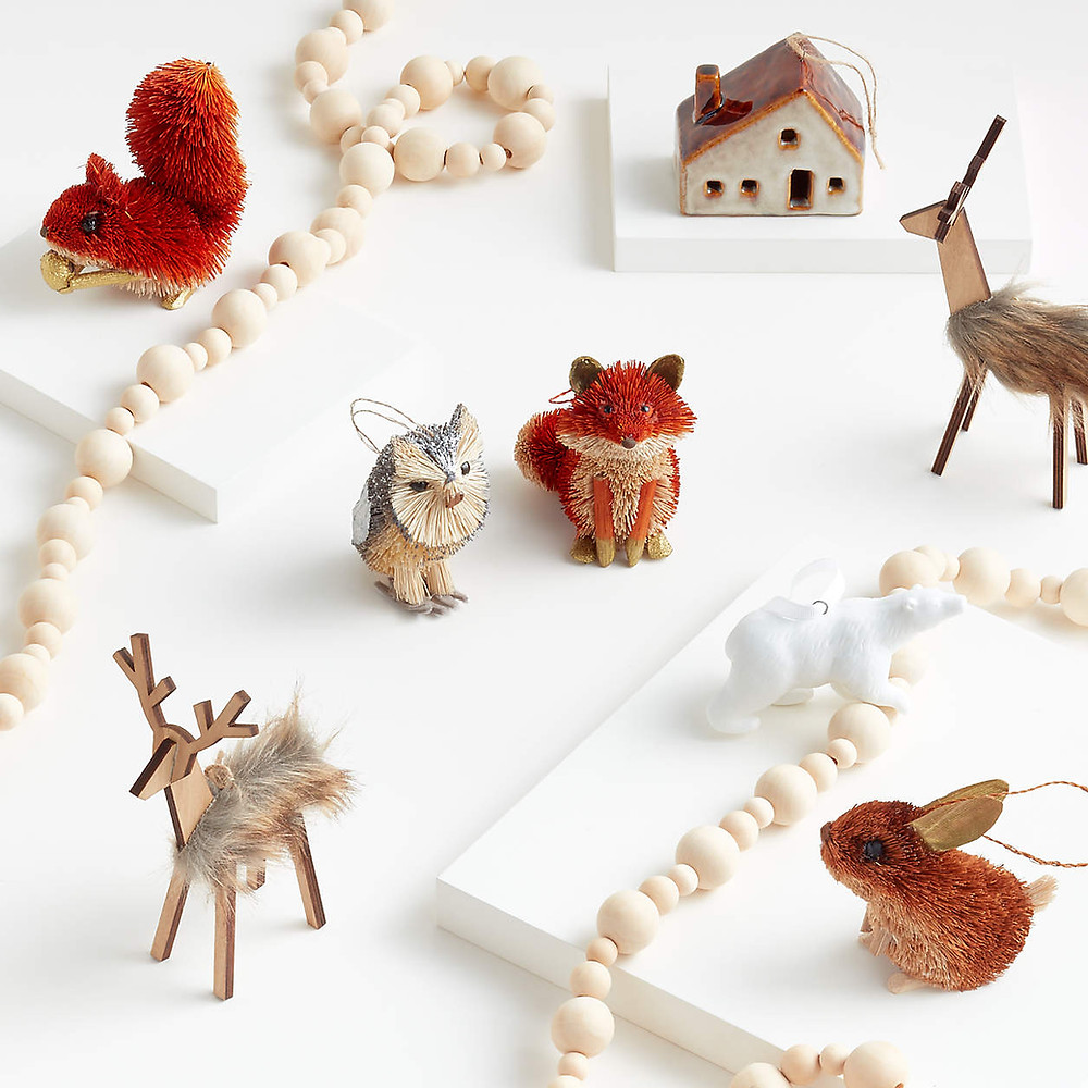 A wooden beaded garland laying amongst scandinavian inspired Christmas ornaments in the shape of forest animals like squirrels, foxes, deer and rabbits for a minimal and modern holiday decor look.