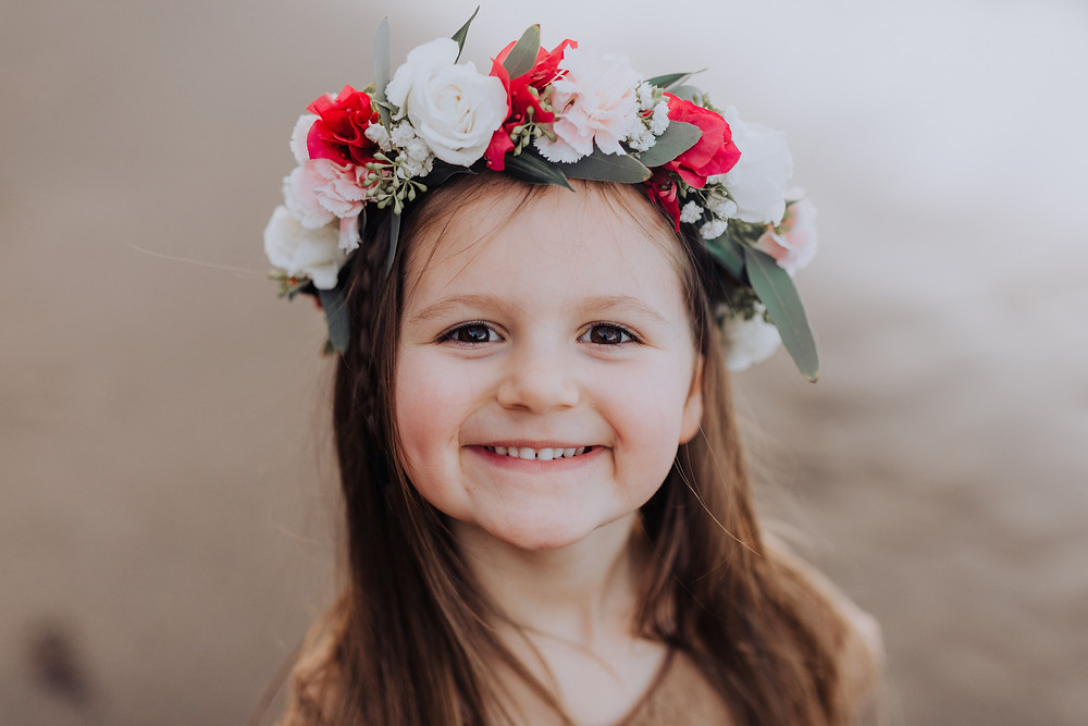 A little girl smiles playfully at the camera with a flower crown in her hair.
