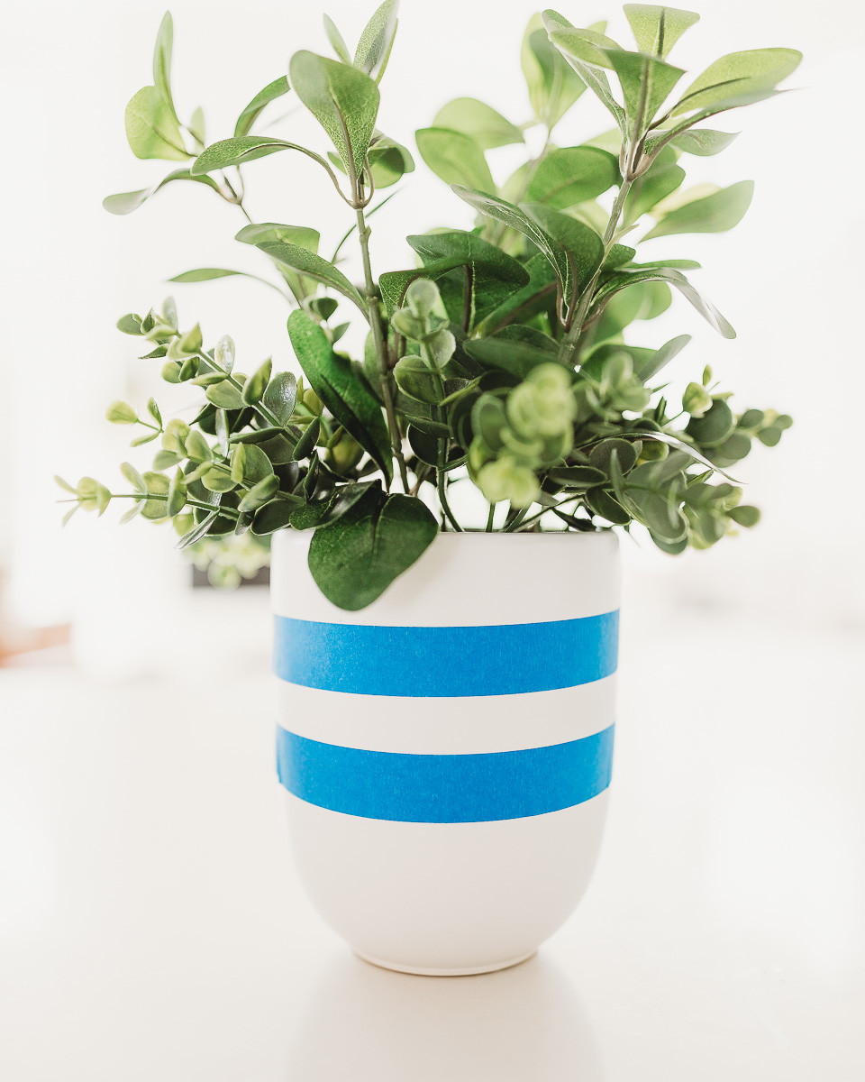 A plant pot with painters tape wrapped around in stripes.